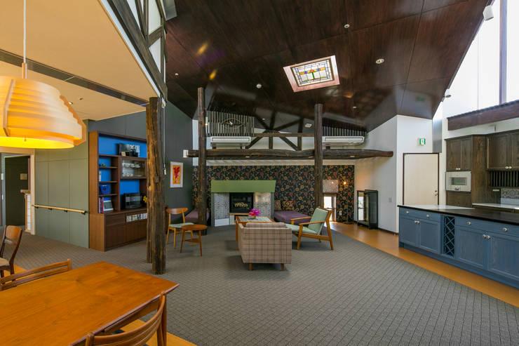 暖炉とニッチのあるリビングとダイニング: 有限会社加々美明建築設計室が手掛けたリビングです。