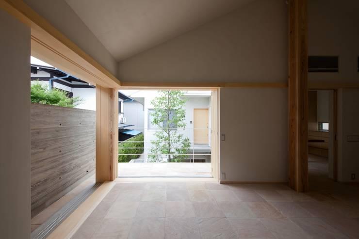 全開できる木製サッシを開け放すと中庭と一体になるリビング!: 根岸達己建築室が手掛けたリビングです。,