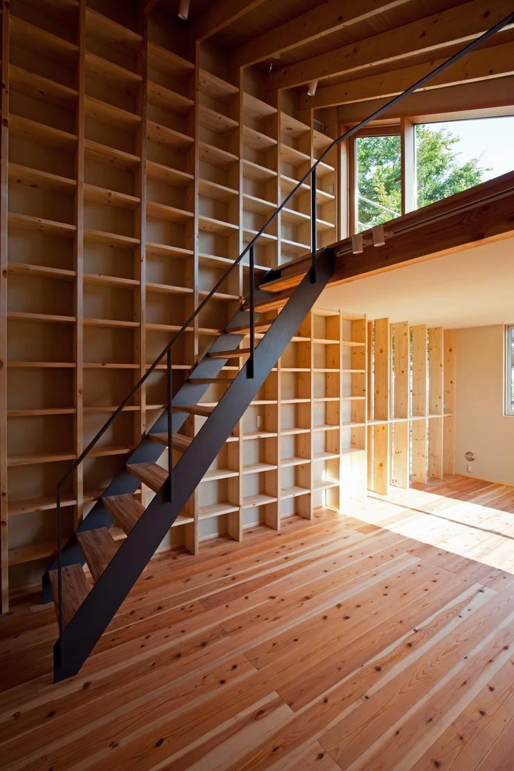 リビングの壁面一杯に本棚を造りました。階段を上ると屋上です!: 根岸達己建築室が手掛けたリビングです。