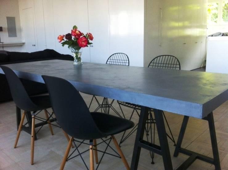 Table en béton ciré, associé à l'acier: Salle à manger de style  par CATHERINE PENDANX