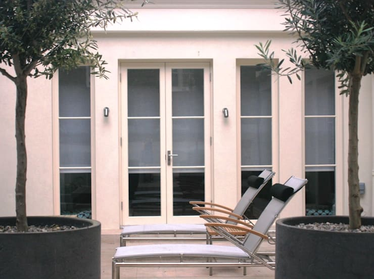 Loungers and Olive trees in the lower atrium by Rae Wilkinson: minimalistic Garden by Rae Wilkinson Design Ltd