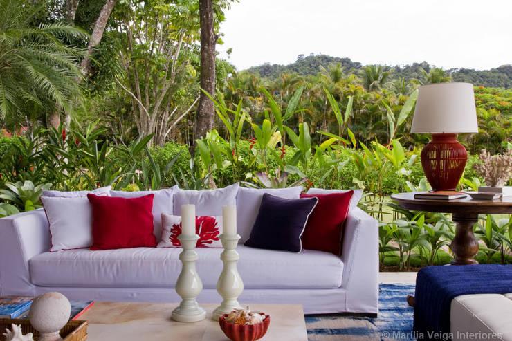 Living + Natureza: Salas de estar tropicais por Marilia Veiga Interiores