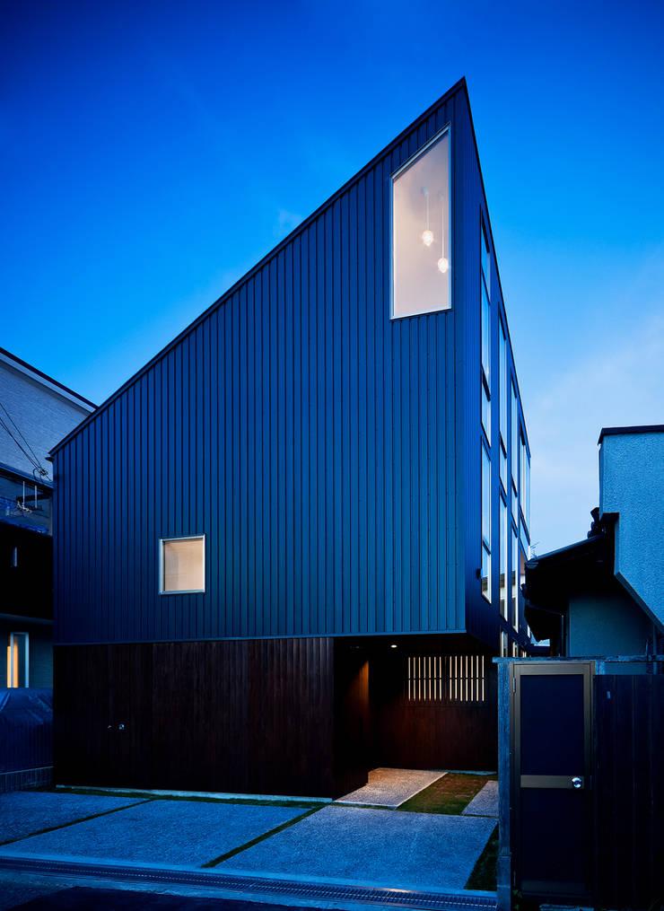 夕景、小窓からペンダントのライトがもれる: UZUが手掛けた家です。