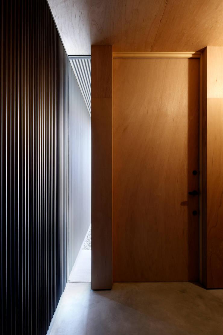 玄関ホール: 道家洋建築設計事務所が手掛けた窓です。,