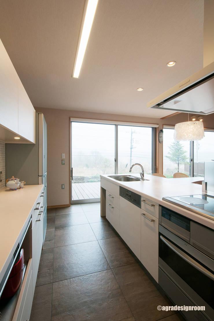 大きなタイル貼りの白いキッチン: アグラ設計室一級建築士事務所 agra design roomが手掛けたキッチンです。