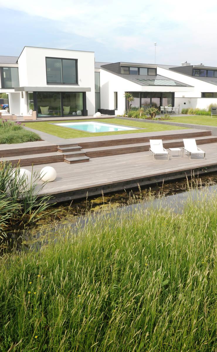 Grote vlakken en lange lijnen sluiten maken koppeling met polderlandschap:  Tuin door Andrew van Egmond (ontwerp van tuin en landschap), Minimalistisch
