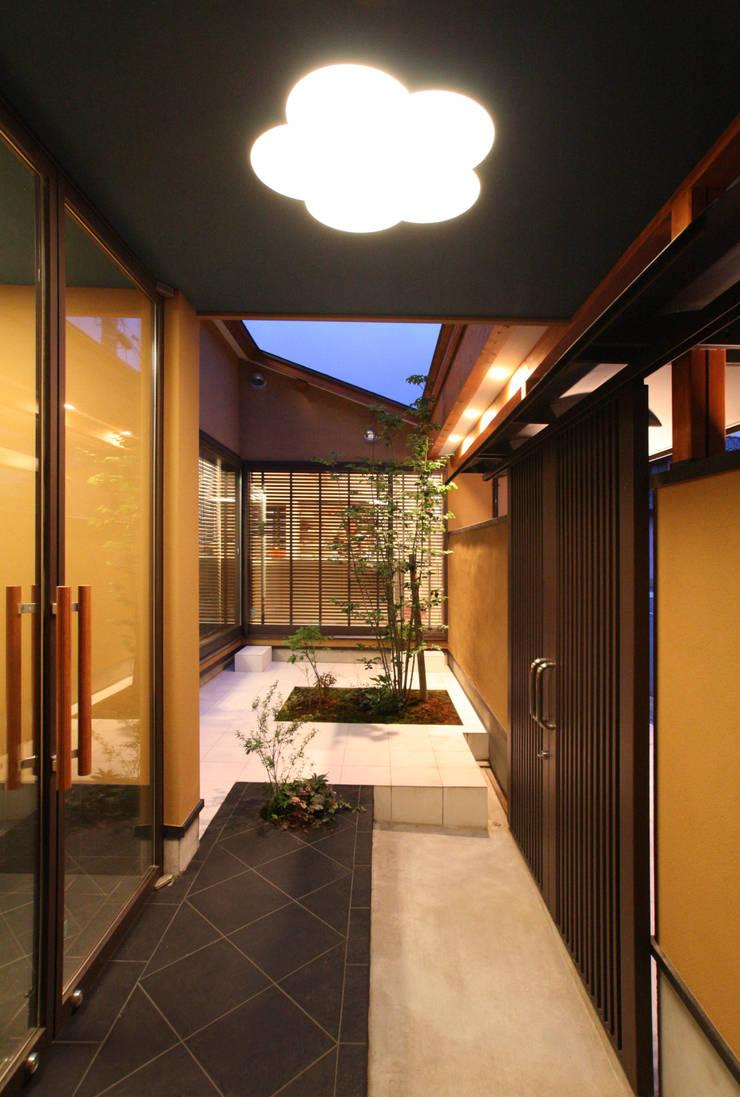 玄関前の空間から中庭を見る: 杉山真設計事務所が手掛けた庭です。