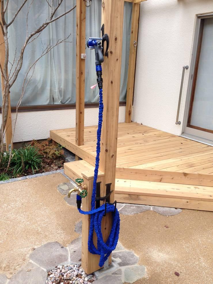 木製立水栓、アイアンのホースハンガー・シャワーホルダー: 株式会社アフロとモヒカンが手掛けた庭です。,