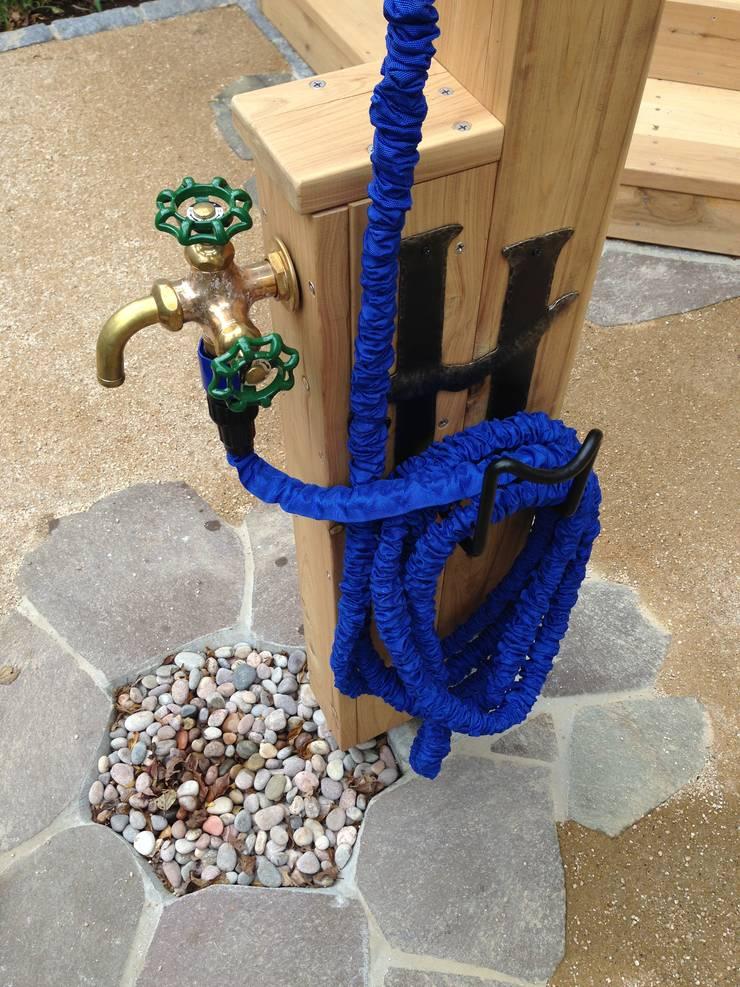 木製立水栓、アイアンのホースハンガー: 株式会社アフロとモヒカンが手掛けた庭です。,
