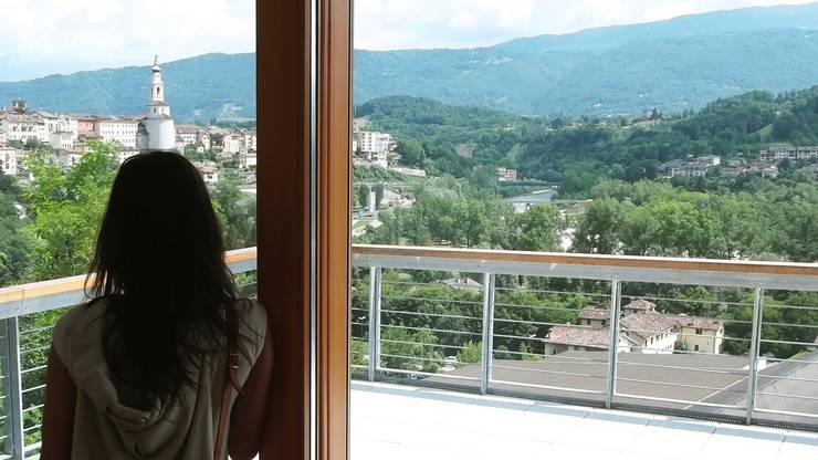 La grande vetrata Sud con l'affaccio sulla città vecchia di Belluno: Soggiorno in stile  di Team Replan - Bortoluzzi Associati
