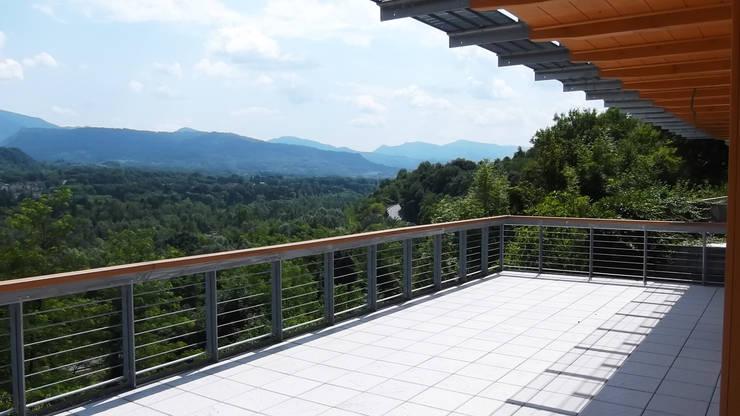 La grande terrazza esterna e la vista sulla valle del Piave: Terrazza in stile  di Team Replan - Bortoluzzi Associati