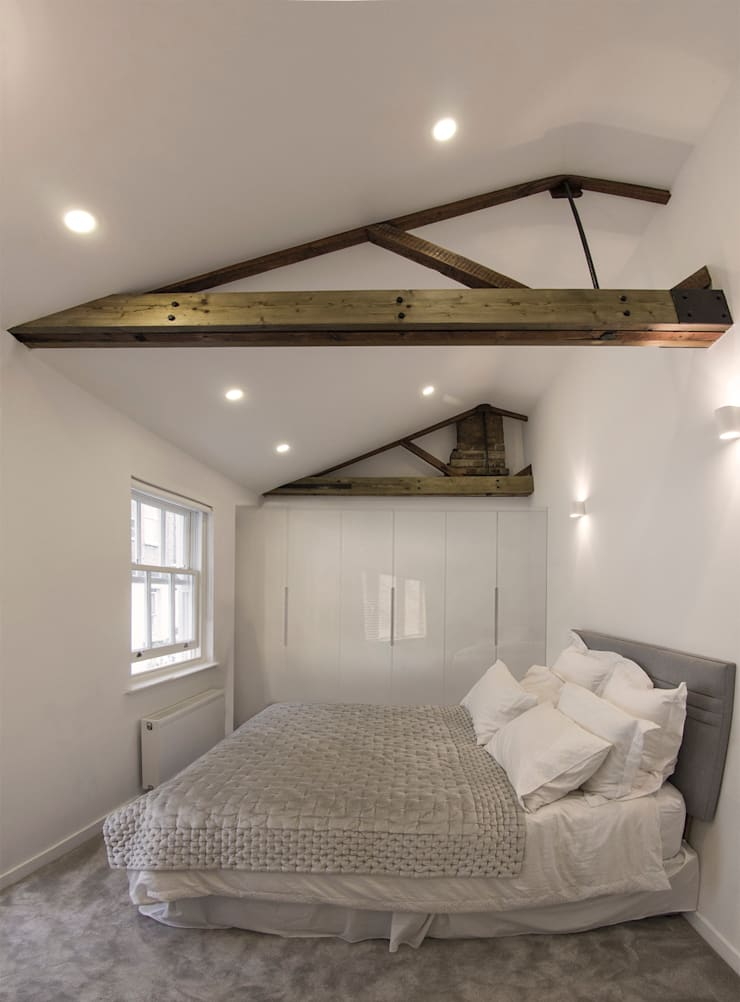 Bedroom with exposed roof timbers and vaulted ceilings :  Bedroom by R+L Architect