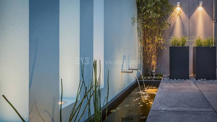 Muur met waterelement en doorkijkvensters:  Tuin door ERIK VAN GELDER | Devoted to Garden Design