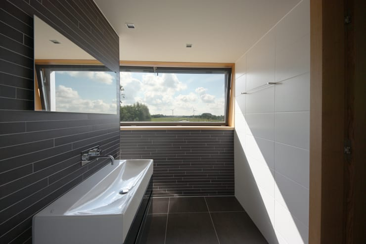 Badkamer met uitzicht over de polder:  Badkamer door VVKH Architecten
