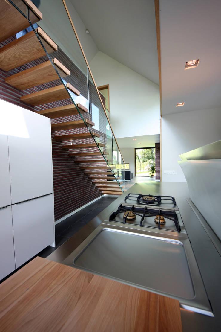 uitkragende trap en glazen balustrade:  Keuken door VVKH Architecten