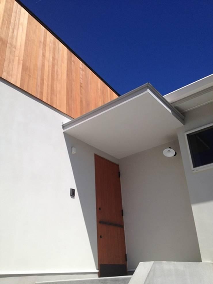 シンプルなアイアンハンドルの玄関ドア: みゆう設計室が手掛けた窓です。