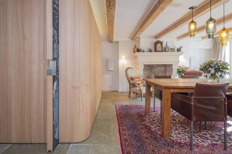 De nieuwe iepenhouten kern met grote krijtbord schuifdeur: eclectische Eetkamer door CUBE architecten