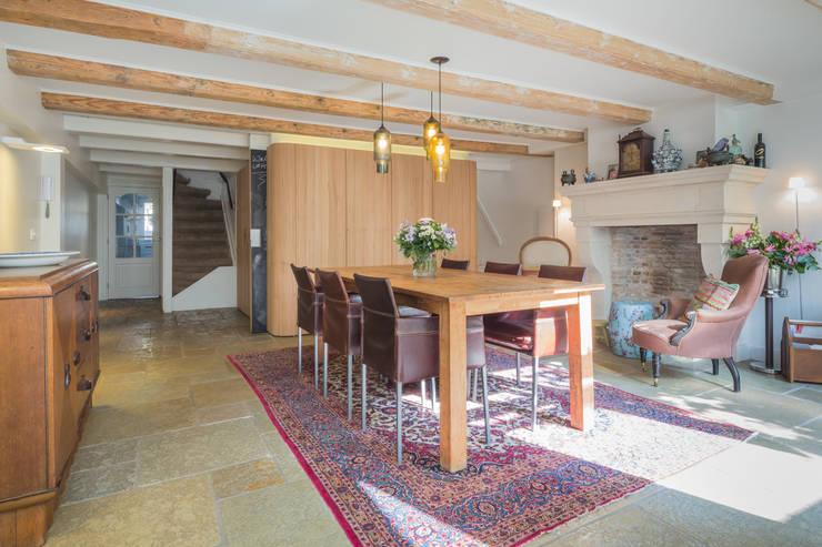 De eetkamer met de moderne kern als meubel in de oude woning:  Eetkamer door CUBE architecten,