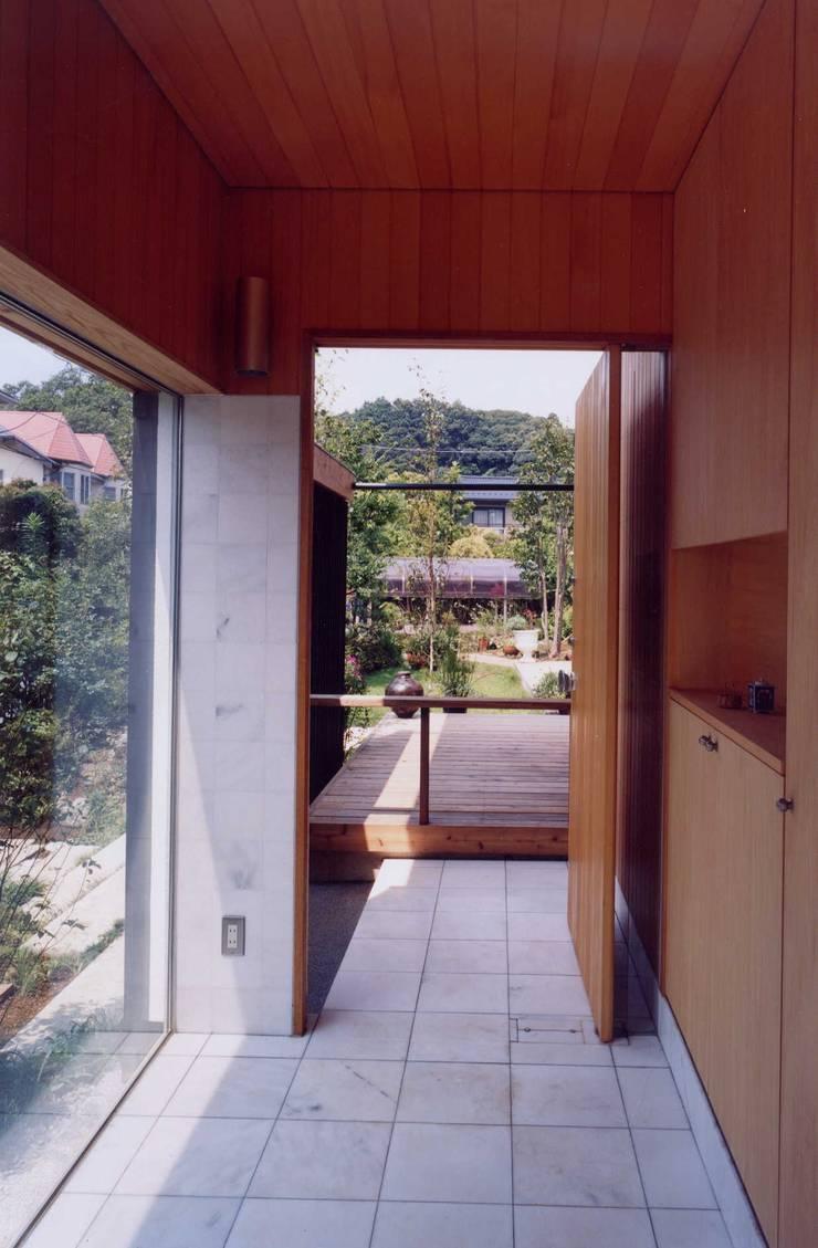 玄関から外を見る: 有限会社加々美明建築設計室が手掛けた庭です。