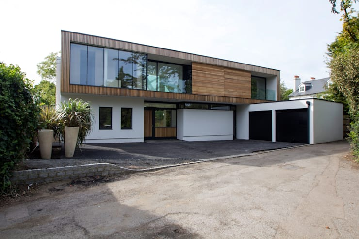 The front elevation with timber-clad upper floor: modern Houses by Hale Brown Architects Ltd