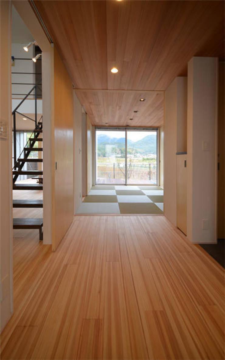 玄関-客間: トミオカアーキテクトオフィスが手掛けた壁です。