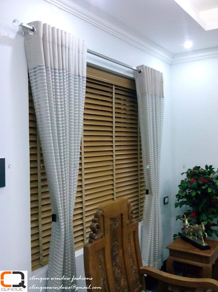wooden blinds with curtain over lap:  Living room by Clinque window blind systems