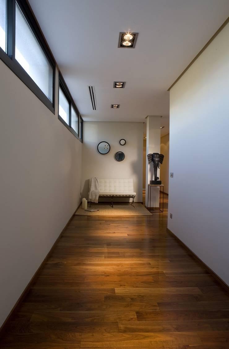 Pasillo con ventanales superiores para garantizar la iluminación y preservar la intimidad: Pasillos y vestíbulos de estilo  de Laura Yerpes Estudio de Interiorismo