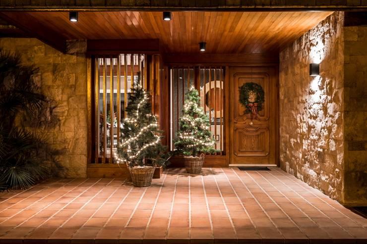 Entrada a la casa con decoración navideña: Casas de estilo  de Laura Yerpes Estudio de Interiorismo