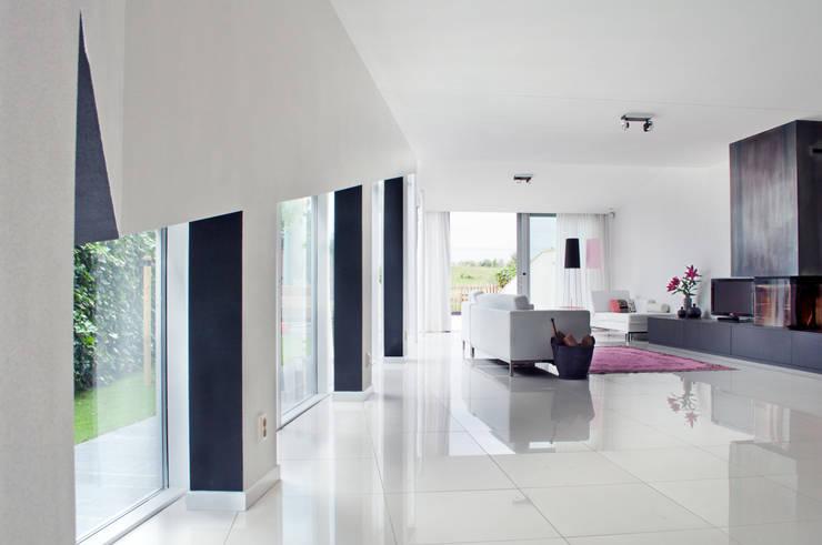 zwarte muren framen het uitzicht naar buiten:  Woonkamer door IJzersterk interieurontwerp