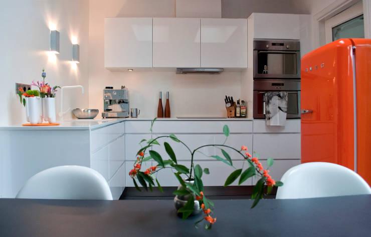 Witte keuken met oranje accent: moderne Keuken door IJzersterk interieurontwerp
