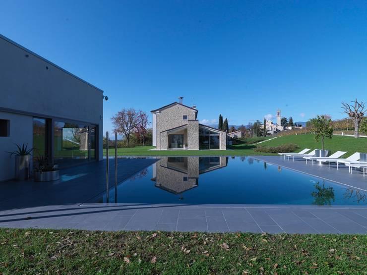 renovation in North Italy: Piscina in stile in stile Moderno di Vegni Design