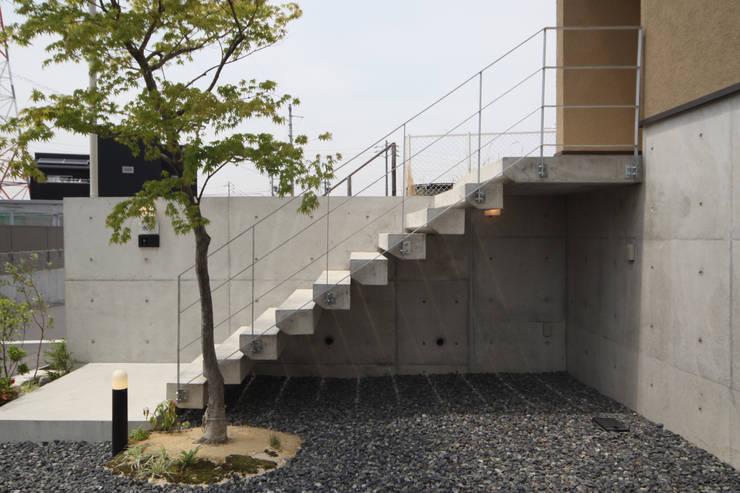 アプローチのコンクリート片持ち階段: 青木昌則建築研究所が手掛けた家です。