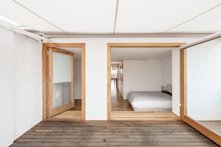 """Reforma de un ático en el barrio del """"Eixample"""" en Barcelona: Dormitorios de estilo minimalista de Room Global"""