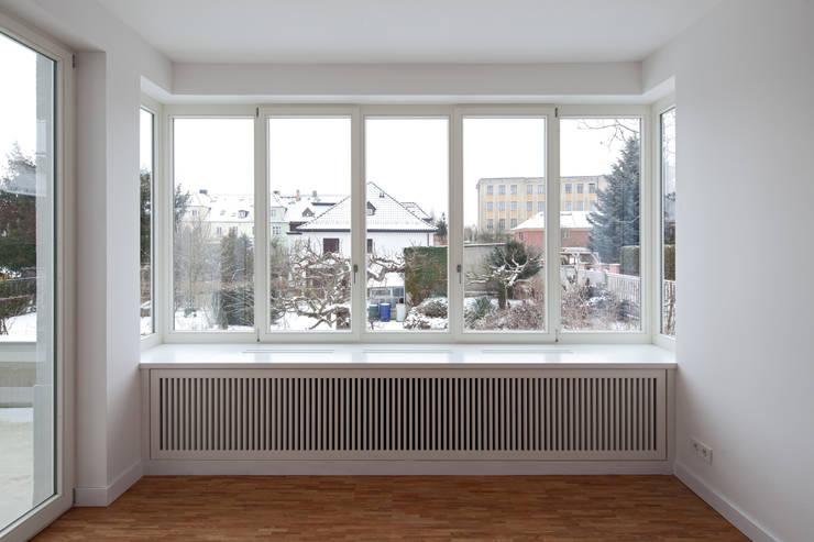 Das Verandafenster des neuen Gartenanbaus: klassische Wohnzimmer von Eingartner Khorrami Architekten BDA