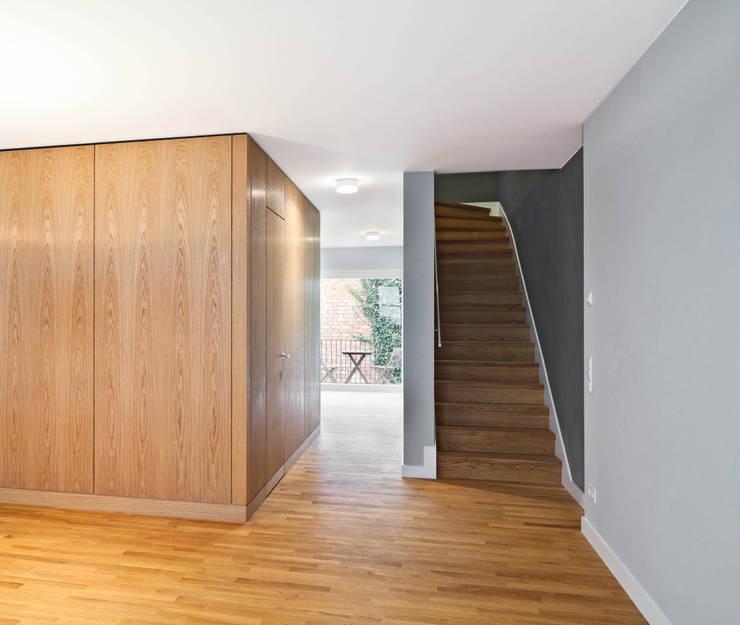 Die Holzbox mit Garderobe und WC strukturiert das loftartige Hauptgeschoss: moderne Wohnzimmer von Eingartner Khorrami Architekten BDA