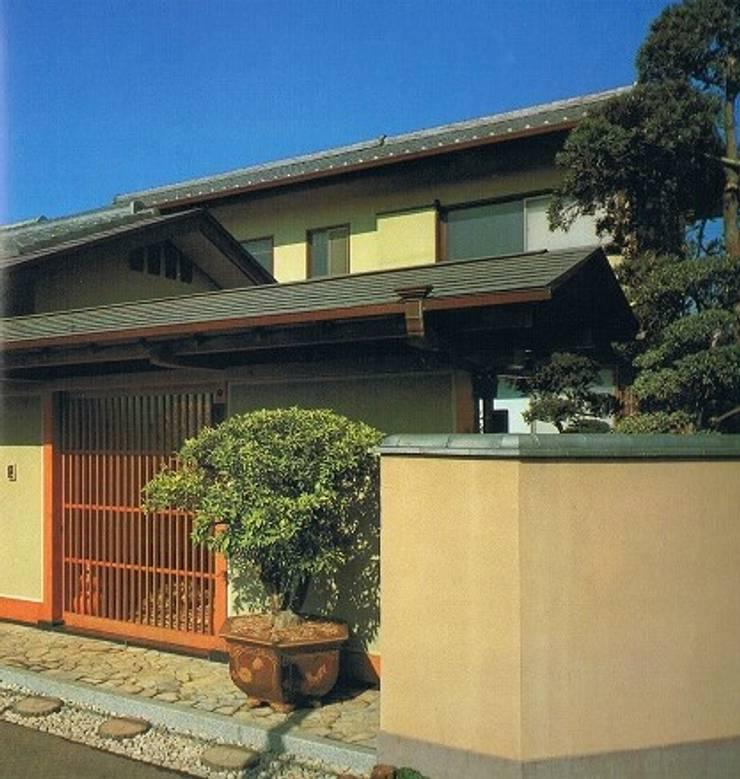 南北に細長い中庭の混在する現代数寄屋の家外観玄関前: 株式会社 山本富士雄設計事務所が手掛けた家です。