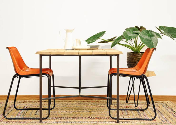 Mesa de madera maciza de eucalipto y acero. Sillas de cuero natural.: Comedor de estilo  de Cube Deco