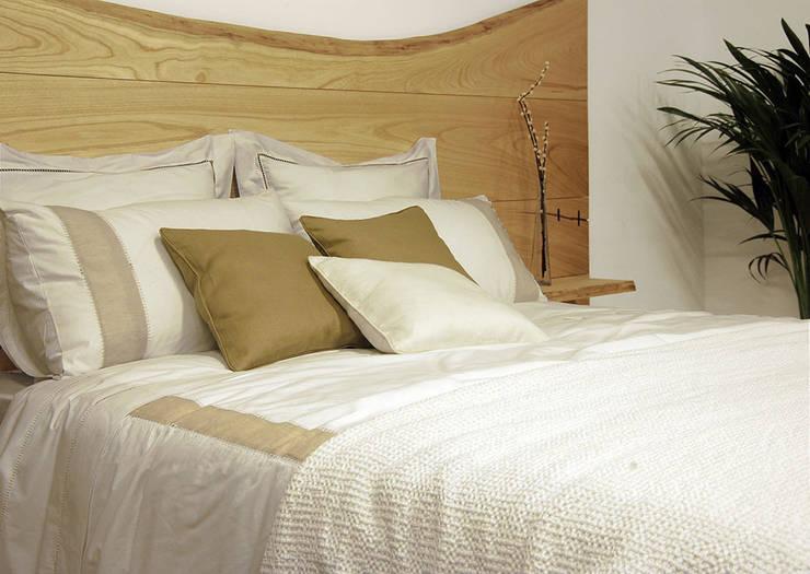 Cabecero de madera maciza de castaño, con mesillas en los laterales.: Dormitorios de estilo  de Cube Deco