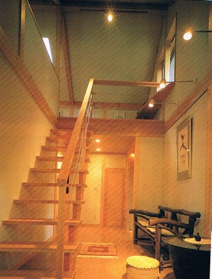 緑多い敷地に建つ小屋裏ギャラリー・アトリエのある家階段室: 株式会社 山本富士雄設計事務所が手掛けた廊下 & 玄関です。