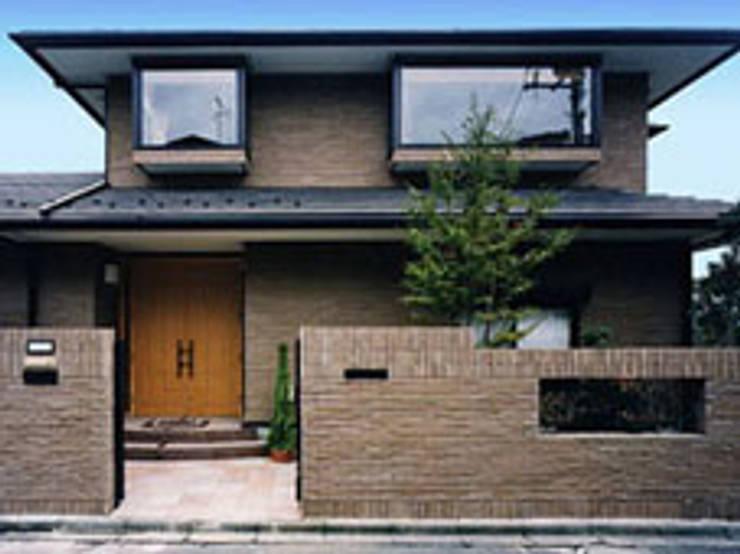 聖蹟桜ヶ丘の重厚な外観総タイル張りの家、正面玄関外観: 株式会社 山本富士雄設計事務所が手掛けた家です。