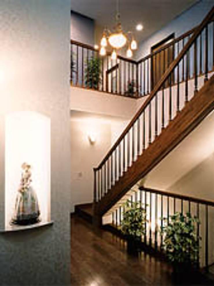 聖蹟桜ヶ丘の重厚な外観総タイル張りの家階段室: 株式会社 山本富士雄設計事務所が手掛けた廊下 & 玄関です。