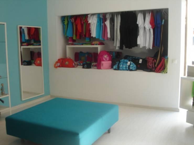 Zona de exposição de roupa: Escritório e loja  por Traço Magenta - Design de Interiores