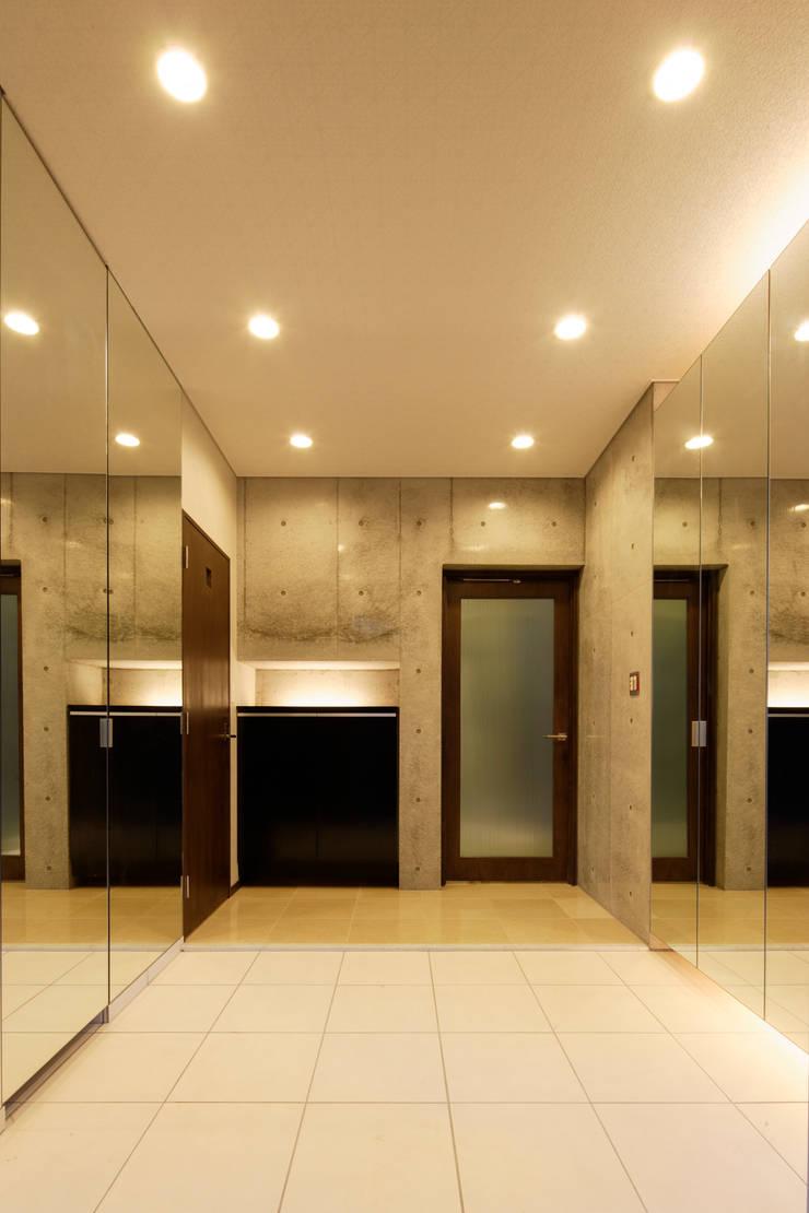 シューズクローゼットの扉を鏡貼りとした開放的な玄関: 鈴木賢建築設計事務所/SATOSHI SUZUKI ARCHITECT OFFICEが手掛けた廊下 & 玄関です。,モダン