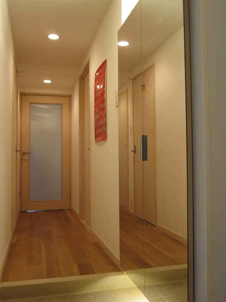 マンションの玄関に広がりを与えるミラーと間接照明: 鈴木賢建築設計事務所/SATOSHI SUZUKI ARCHITECT OFFICEが手掛けた玄関&廊下&階段です。