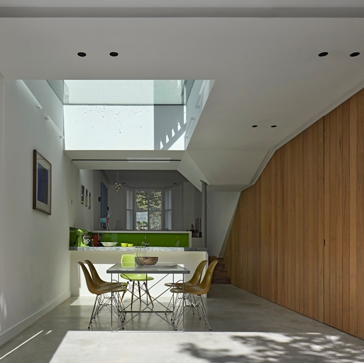 Dining and Kitchen space with folded planes and skylight:  Dining room by Neil Dusheiko Architects