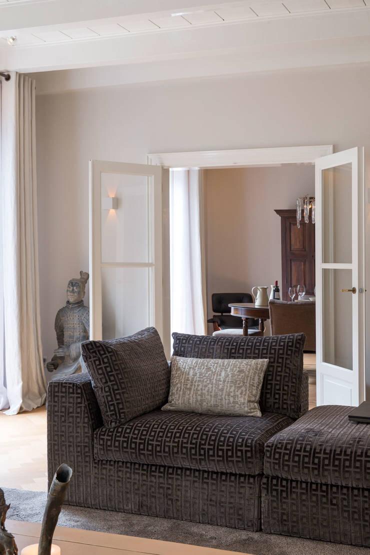 doorkijk naar woonkeuken:  Woonkamer door choc studio interieur