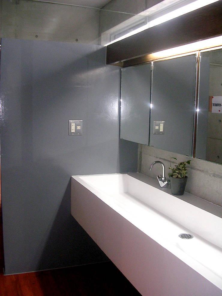 洗面カウンター: Arms DESIGNが手掛けた浴室です。