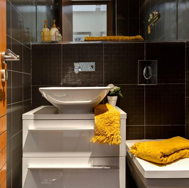 Black, yellow and white creates a stylish modern bathroom in a compact area.:  Bathroom by Design by Deborah Ltd