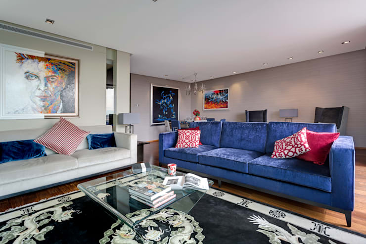 Modern lounge with a bright pop of velvet blue:  Living room by Design by Deborah Ltd