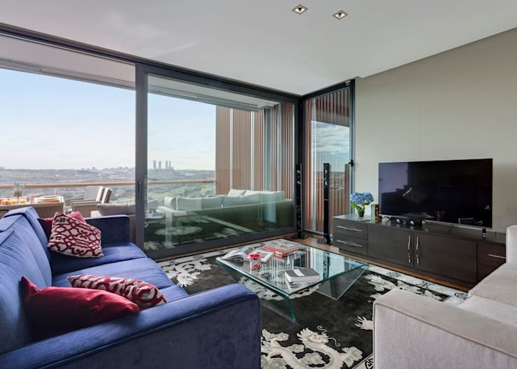 A comfortable family lounge overlooking the Madrid skyline.:  Living room by Design by Deborah Ltd